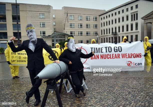 Picture taken on September 13 2017 shows activists of the International campaign to abolish Nuclear Weapons wearing masks of US President Donald...