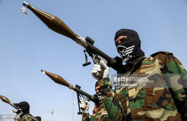 A picture taken on September 16 2017 shows masked members of the Imam Ali Division one of the groups fighting within the Hashed alShaabi...