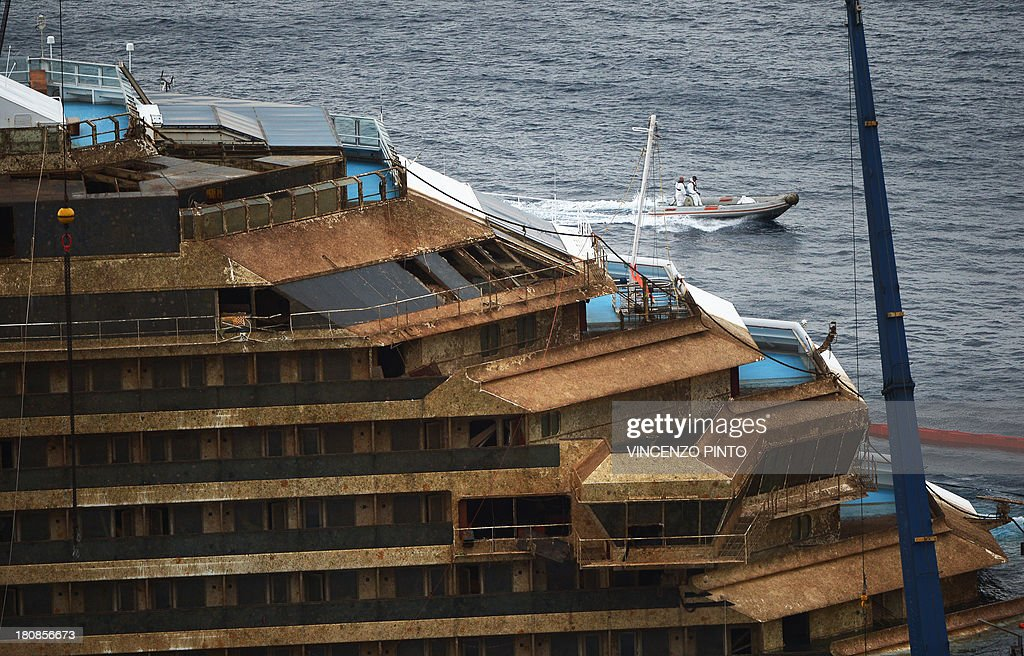 A picture taken on September 17, 2013 shows the wreck of Italy's Costa Concordia cruise ship which begins to emerge from water near the harbour of Giglio Porto. Salvage operators in Italy lifted the Costa Concordia cruise ship upright from its watery grave off the island of Giglio on Tuesday in the biggest ever project of its kind. Thirty-two people died when the ship, with 4,200 passengers onboard, hit rocks and ran aground off the island of Giglio on January 2012.