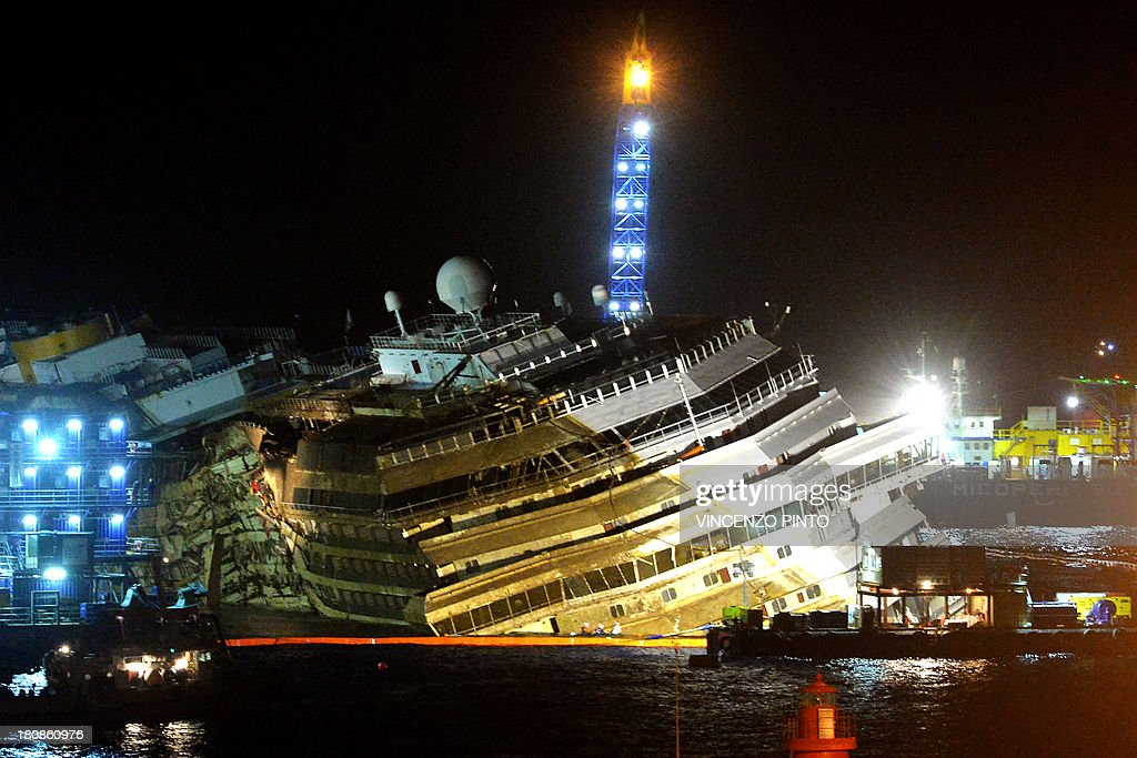 A picture taken on September 17, 2013 shows the wreckage of Italy's Costa Concordia cruise ship which begins to emerge from water near the harbour of Giglio Porto. Salvage operators in Italy lifted the Costa Concordia cruise ship upright from its watery grave off the island of Giglio on Tuesday in the biggest ever project of its kind. Thirty-two people died when the ship, with 4,200 passengers onboard, hit rocks and ran aground off the island of Giglio on January 2012.