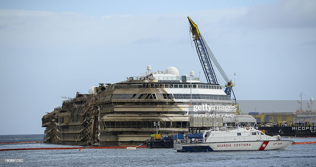 A picture taken on September 17, 2013 shows the wreckage of Italy's Costa Concordia cruise ship which begins to emerge from water near the harbour of Giglio Porto Salvage operators in Italy lifted the Costa Concordia cruise ship upright from its watery grave off the island of Giglio in the biggest ever project of its kind. The ship's horn sounded for the first time since the January 13, 2012 tragedy, its sound mixing with applause and cheers in the port in a dramatic climax to the massive salvage operation. Local residents and survivors spoke of an eerie feeling as the ship rose, saying the sight reminded them of the tragedy that claimed 32 lives.