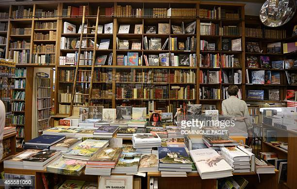 Picture taken on September 17 2014 shows a woman looks at books inside the bookshop Delamain the oldest bookshop of Paris The clients of the oldest...