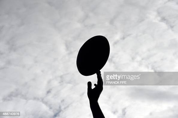 A picture taken on September 17 2015 shows the silhouette of a detail of a statue of a rugby player reaching for a ball outside Twickenham Stadium...