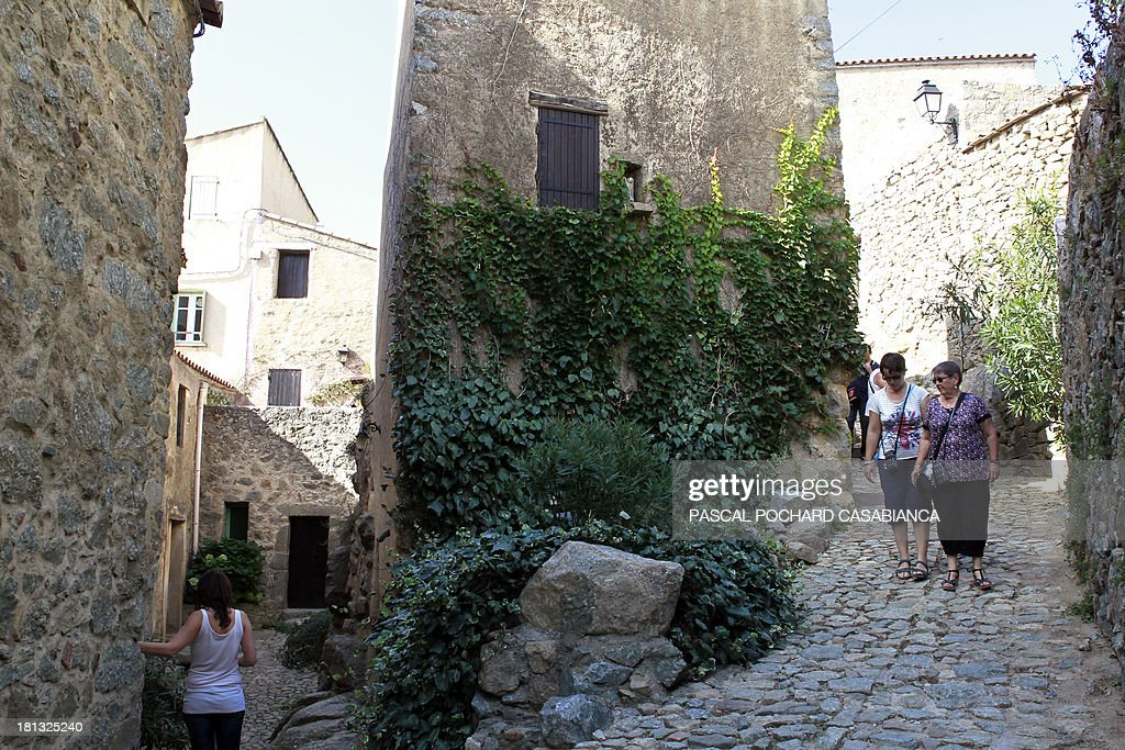 A picture taken on September 19, 2013 shows people walking along alleys in San Antonino village, on the French Mediterranean island of Corsica. San Antonino is listed as one of the most beautiful villages of France.
