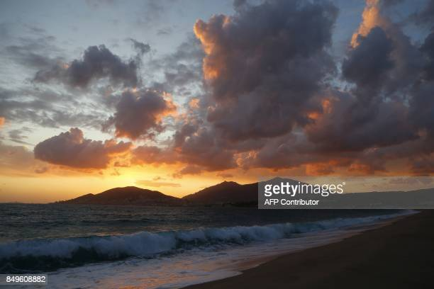 Picture taken on September 19 2017 show sunset on the Ricanto beach as Ajaccio is seen in the background on September 19 2017 on the French...