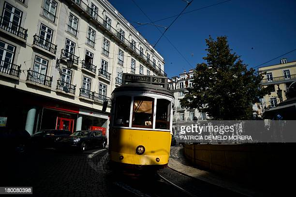 A picture taken on September 2 2013 shows a tram passing by Camoes Square in Lisbon 'Tourism in Portugal has experienced over the past months the...