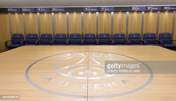A picture taken on September 2 2014 shows the Paris Saint Germain football club players' seats and a table with the club's logo in the locker room of...