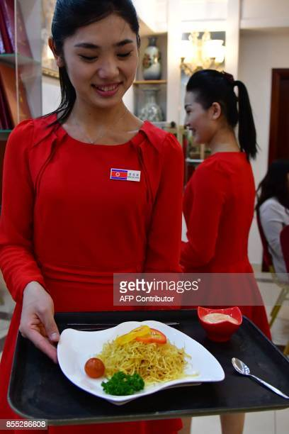 A picture taken on September 21 2017 shows a waitress serving a dish to patrons at the Pyongyang Okryugwan a North Korean restaurant in Dubai On any...
