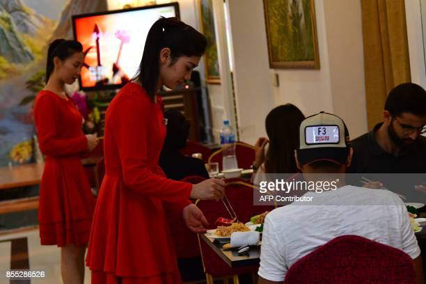 A picture taken on September 21 2017 shows waitresses serving dishes to patrons at the Pyongyang Okryugwan a North Korean restaurant in Dubai On any...