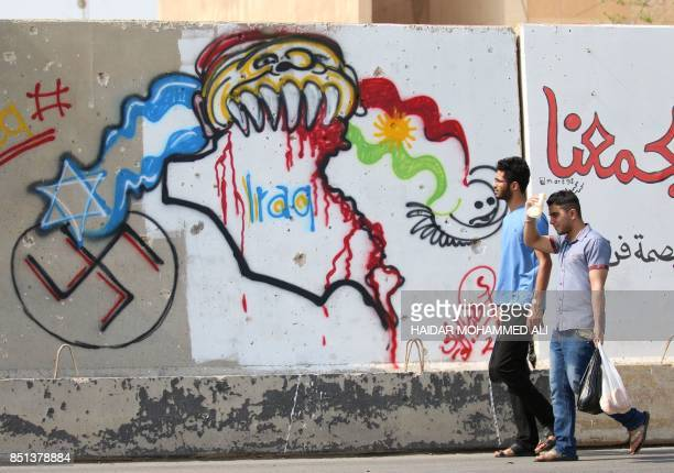 A picture taken on September 22 2017 in the southern Iraqi city of Basra shows men walking past a graffiti on a wall drawn by Iraqi cartoonist Arkan...