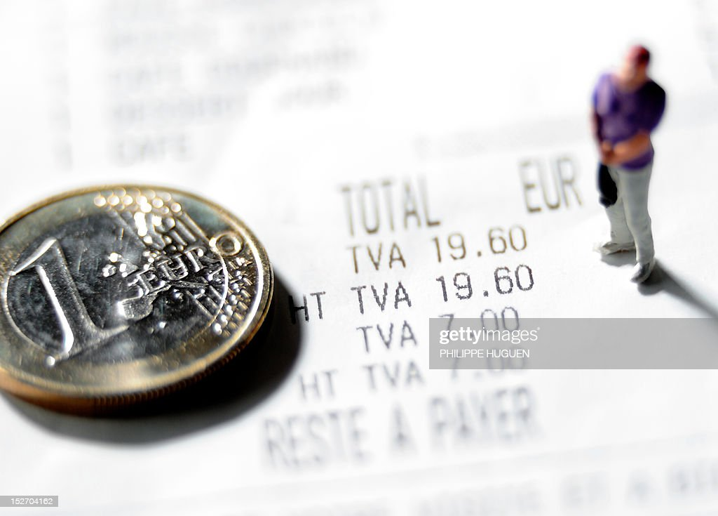 A picture taken on September 24, 2012 in Lille, shows an illustration made with a figurine and a one Euro coin set up on a receipt indicating the 7 percent rate of the Value Added Tax (VAT or TVA in French).