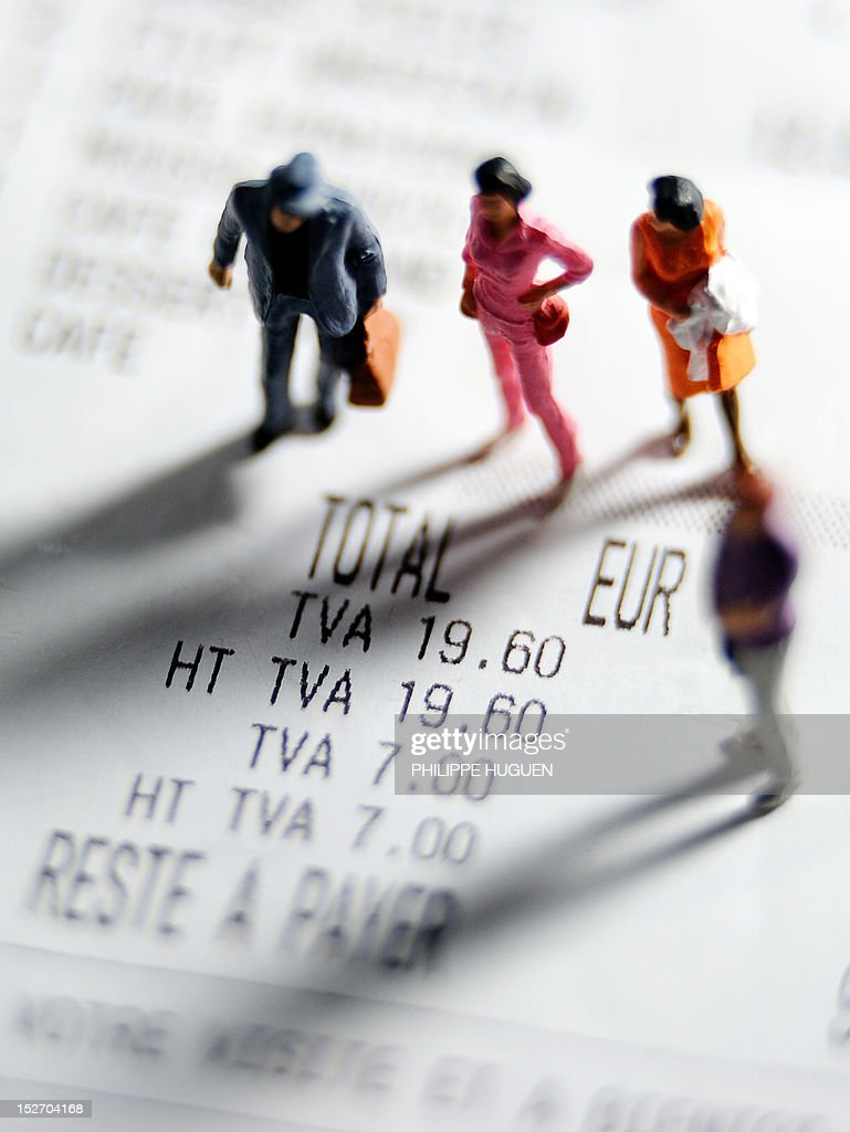 A picture taken on September 24, 2012 in Lille, shows an illustration made with figurines set up on a receipt indicating the 7 percent rate of the Value Added Tax (VAT or TVA in French).
