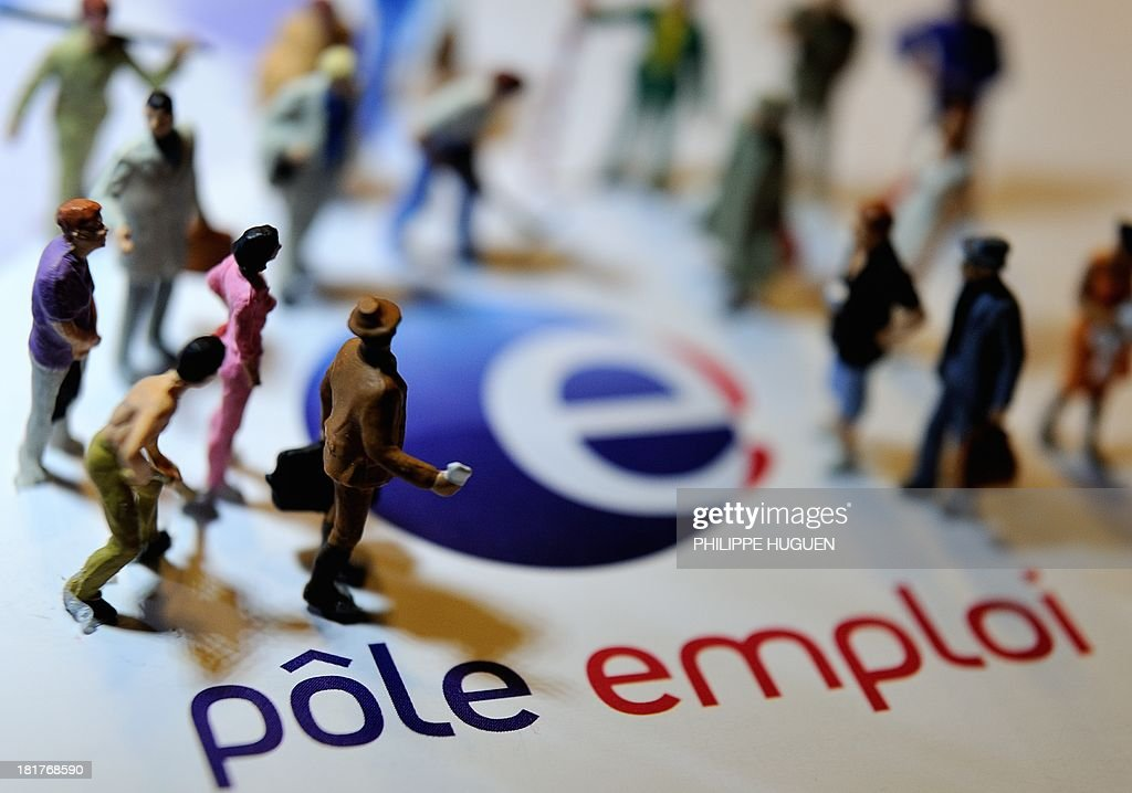 A picture taken on September 25, 2013 in Lille, shows an illustration made with figurines symbolizing workers of different professions set on the logo of 'Pole emploi', the French governmental agency aiming at helping unemployed people to find jobs and providing them with financial aid .