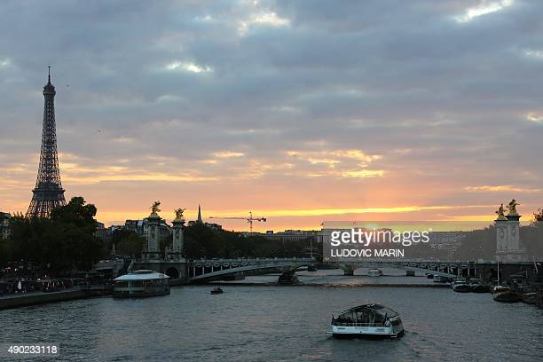 Picture taken on September 26 2015 shows a tourist boat on the River Seine approching the Alexandre III bridge and Eiffel Tower at sunset in the...