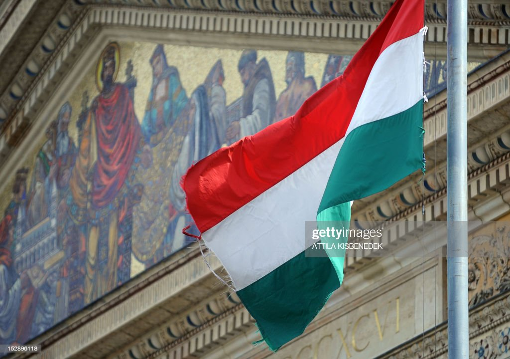 A picture taken on September 27, 2012 shows the Hungarian flag in front of the Mucsarnok, the Fine Arts Museum at Heroes square in Budapest with a mosaic picture of Saint Stephen I, the first King of Hungary. AFP PHOTO / ATTILA KISBENEDEK