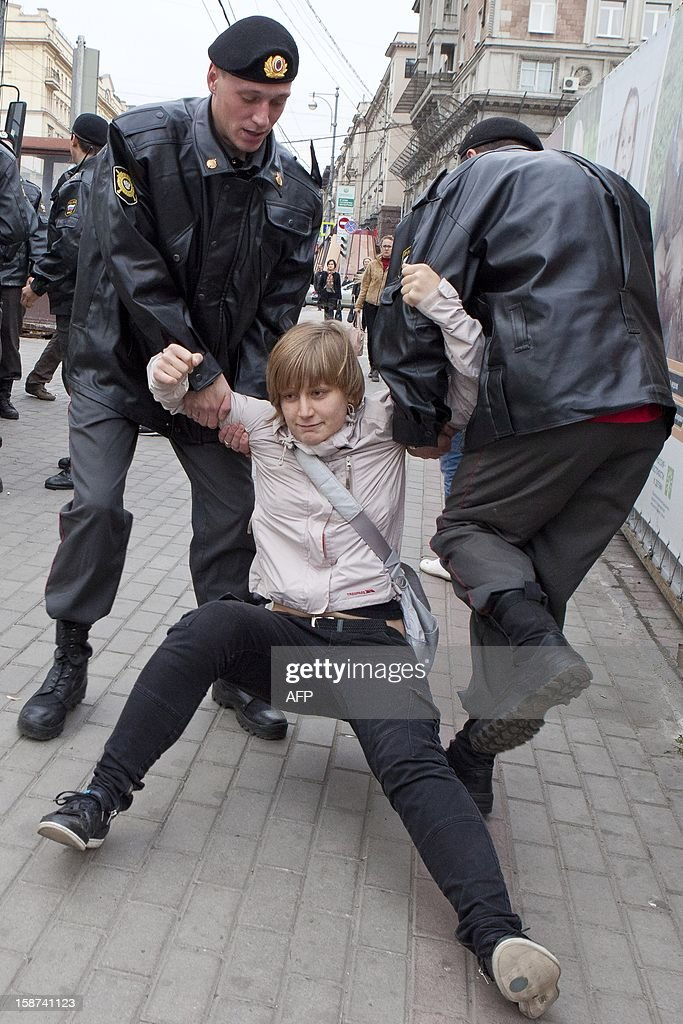 A picture taken on September 27, 2011, shows Anastasiya Rybachenko (C), a member of Solidarity opposition movement, being detained by a police officers during an opposition rally in Moscow. During the May 6 rally, which turned suddenly violent one day before Putin's inauguration, Rybachenko argued with police through a loudspeaker asking them to release detainees. Later when police searched her apartment as she was in Europe, Rybachenko decided not to come back.