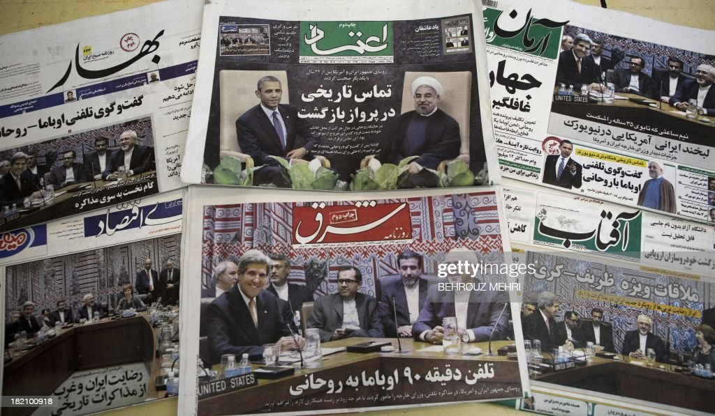 A picture taken on September 28, 2013 in Tehran shows Iranian newspapers with pictures depicting Iranian President Hassan Rouhani, US President Barack Obama, Iranian Foreign Minister Mohammad Javad Zarif and his American counterpart John Kerry. Iranian newspapers hailed the first contact between presidents Rouhani and Obama but warned that opponents like arch-foe Israel would seek to torpedo the historic opening to Washington. AFP PHOTO/BEHROUZ MEHRI