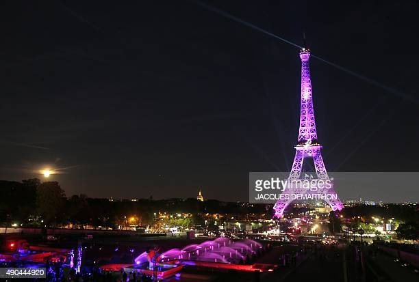A picture taken on September 28 2015 in Paris shows the Eiffel Tower illuminated with a pink light as part of the 'Ruban Rose' event launched by...