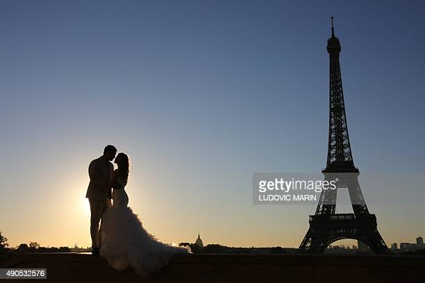 Picture taken on september 29 2015 shows a young married couple posing for souvenirs pictures at sunrise in front of the Eiffel tower on Trocadero...