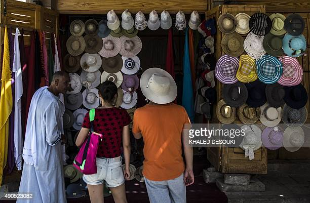 A picture taken on September 29 2015 shows tourists looking at hats displayed at a shop near the Valley of the Kings close to Luxor 500 kms south of...