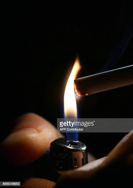 A picture taken on September 29 2017 shows a close up shot of a man lighting a cigarette in Kuwait City On October 1 the United Arab Emirates will...