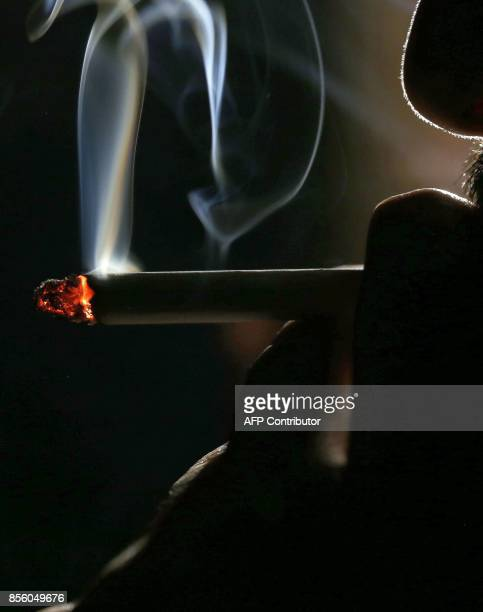A picture taken on September 29 2017 shows a close up shot of a man smoking a cigarette in Kuwait City On October 1 the United Arab Emirates will...