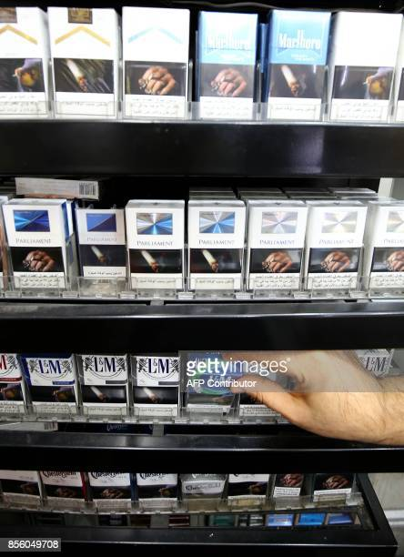 A picture taken on September 29 2017 shows a close up shot of a vendor organizing cigarette boxes at a shop in Kuwait City On October 1 the United...