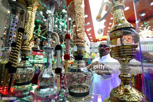 A picture taken on September 29 2017 shows a man inspecting waterpipes at a shop in Kuwait City On October 1 the United Arab Emirates will double the...