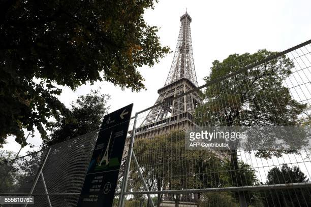 A picture taken on September 29 2017 shows metal gates set up for the construction of bulletproof glass walls set to go up around the Eiffel Tower in...