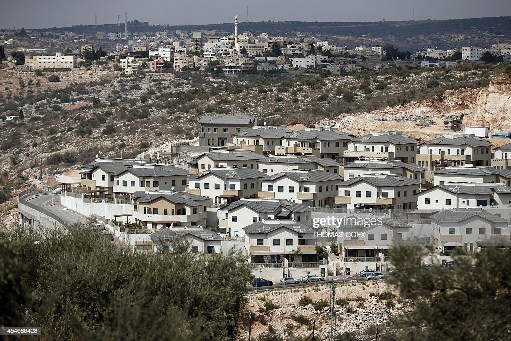 A picture taken on September 5 2014 shows a partial view of the Israeli settlement of Elkana in front of the northwest West Bank village of Saniriya...