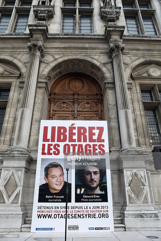 A picture taken on September 6 2013 shows a placard calling for the release of French journalists Didier Francois and Edouard Elias six months after...
