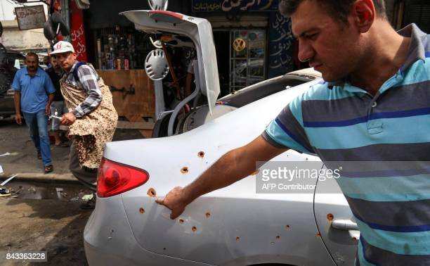A picture taken on September 6 2017 at a garage in east Mosul shows an Iraqi pointing at the bulletriddled body of a car that was damaged during the...