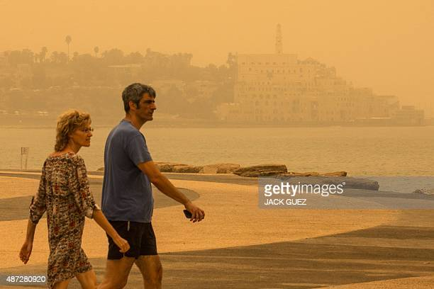 A picture taken on September 8 2015 shows a man and a woman walking in the Israeli coastal city of Tel Aviv during a sandstorm A dense sandstorm...