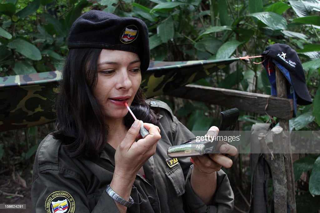 Picture taken on the end of July, 2012 in northern Colombia of a Revolutionary Armed Forces of Colombia (FARC) guerrilla member -of a front of the Martin Caballero bloc of the FARC - EP-, as she puts make up on. Peace talks between the Colombian government and the FARC will have a recess since December 21, 2012 until January 14, informed both delegations in Havana. AFP PHOTO / Dick Emanuelsson