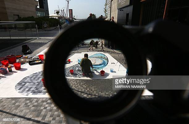 A picture taken though a magnifying lens shows an artist working on his chalk 3D artwork on March 4 2015 near the Jumeirah Beach Residence in Dubai...