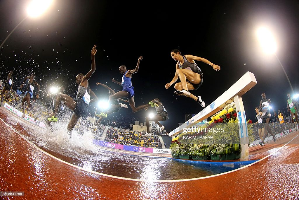 A picture taken through a fisheye lense shows athletes competing in the men's steeplechase during the Diamond League athletics competition at the Suhaim bin Hamad Stadium in Doha, on May 6, 2016. / AFP / KARIM