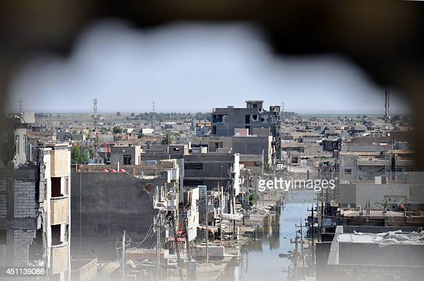 A picture taken through a hole in a wall on June 24 2014 in the city of Ramadi in the Anbar province shows buildings that were damaged during...