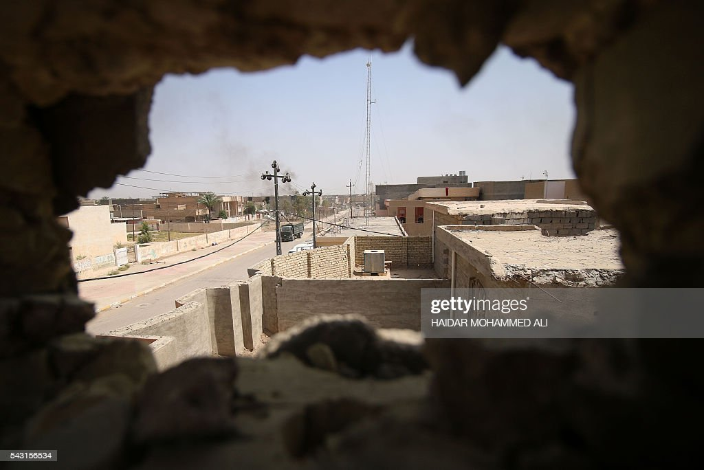 A picture taken through a hole on a building shows Fallujah, 50 kilometres (30 miles) from the Iraqi capital Baghdad, after Iraqi forces retook the embattled city from the Islamic State group on June 26, 2016. Iraqi Prime Minister Haider al-Abadi urged all Iraqis to celebrate the recapture of Fallujah by the security forces and vowed the national flag would be raised in Mosul soon. While the battle has been won, Iraq still faces a major humanitarian crisis in its aftermath, with tens of thousands of people who fled the fighting desperately in need of assistance in the searing summer heat. ALI