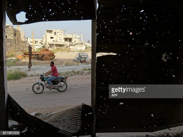 TOPSHOT A picture taken through a metal venetian blind with bullets holes on April 15 2016 shows a man riding his motorbike in a rebelheld area of...