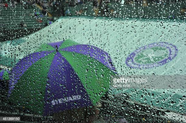 A picture taken through a rain spattered perspex barrier on court 1 shows a steward sheltering under an umbrella on a covered court after rained...