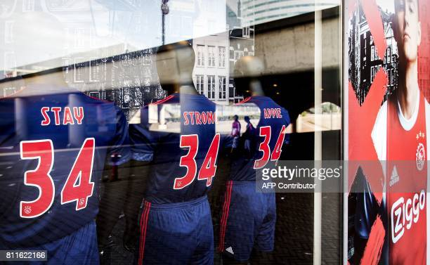 A picture taken through a shop window show football jerseys bearing the words 'Stay Strong Appie' and the number 34 to show support to Ajax...