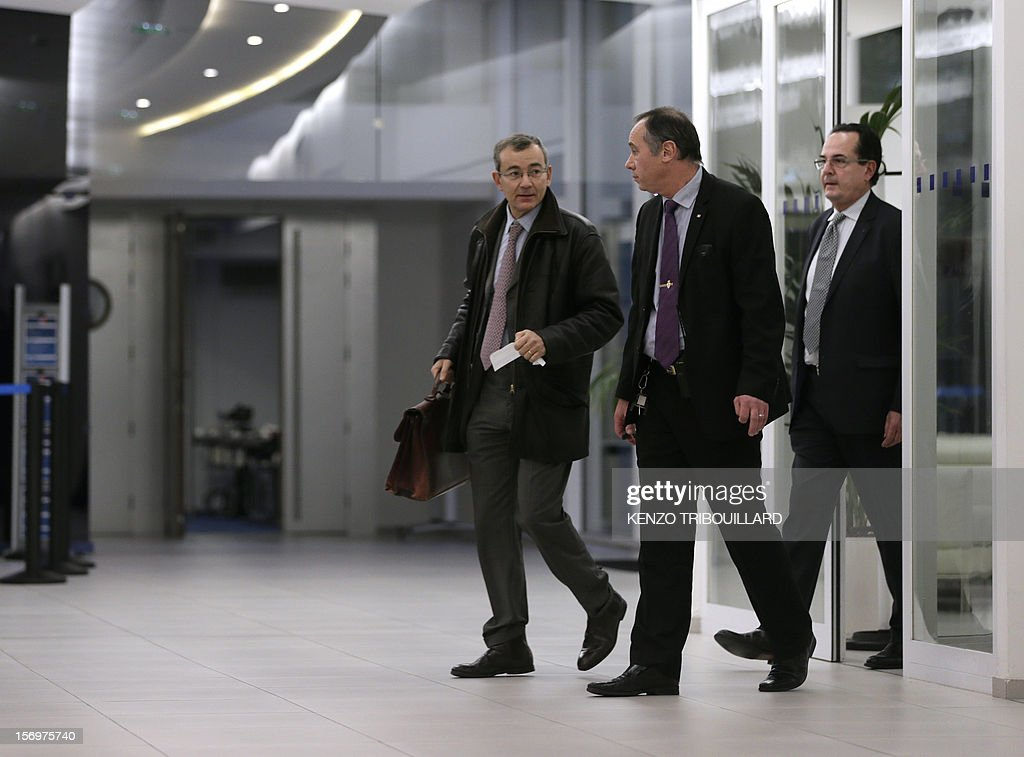A picture taken through a window shows French bailiff Denis Calippe (L) leaving the French opposition UMP right-wing party, on November 26, 2012 in Paris after a working session of the UMP's appeal elections control board which confirmed the decision of the UMP's elections control committee (COCOE) declaring the victory of Jean-Francois Cope as new president of UMP, on November 19, 2012. This appeal followed the failure of the mediation by party heavyweight Juppe, a former premier and foreign minister, with the right-winger, who was declared the winner of November 22 knife-edge vote to pick a party leader, Jean-Francois Cope, and his centrist rival Francois Fillon. AFP PHOTO KENZO TRIBOUILLARD