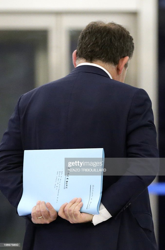A picture taken through a window shows French lawyer Francis Szpiner (R), supporter of Jean-Francois Cope, the new president of French opposition UMP right-wing party, leaving, with a folder named 'procedure' in his hands, on November 26, 2012 in Paris after a working session of the UMP's appeal elections control board which confirmed the decision of the UMP's elections control committee (COCOE) declaring the victory of Cope, on November 19, 2012. This appeal followed the failure of the mediation by party heavyweight Alain Juppe, a former premier and foreign minister, with the right-winger, who was declared the winner of November 22 knife-edge vote to pick a party leader, Jean-Francois Cope, and his centrist rival Francois Fillon. AFP PHOTO KENZO TRIBOUILLARD