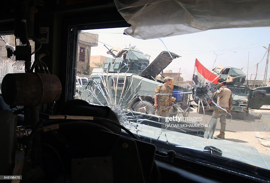 A picture taken through the bullet-riddled windshield of a military vehicle shows Iraqi government forces standing in Fallujah, 50 kilometres (30 miles) from the capital Baghdad, after they retook the embattled city from the Islamic State group on June 26, 2016. Iraqi Prime Minister Haider al-Abadi urged all Iraqis to celebrate the recapture of Fallujah by the security forces and vowed the national flag would be raised in Mosul soon. While the battle has been won, Iraq still faces a major humanitarian crisis in its aftermath, with tens of thousands of people who fled the fighting desperately in need of assistance in the searing summer heat. ALI