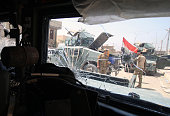 A picture taken through the bulletriddled windshield of a military vehicle shows Iraqi government forces standing in Fallujah 50 kilometres from the...