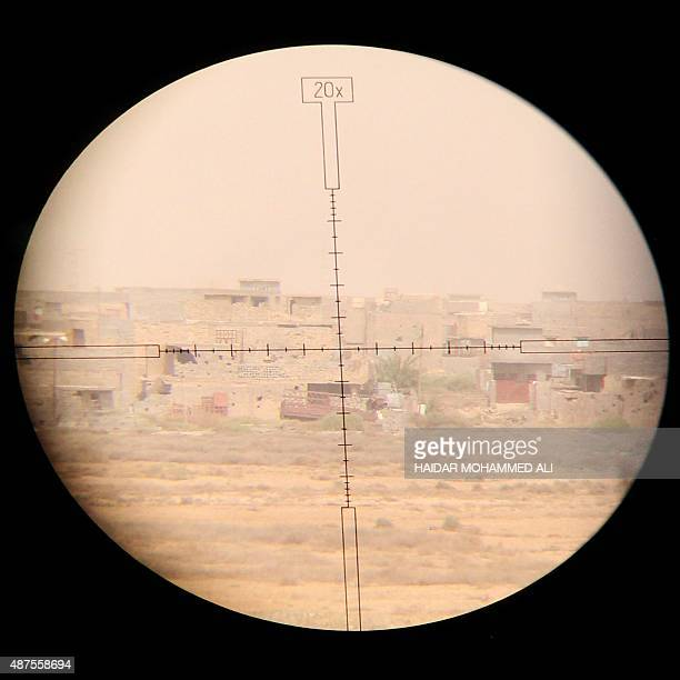 A picture taken through the scope of a counterterrorism unit sniper shows parts of the AlHayakel area on the eastern outskirts of Fallujah during a...