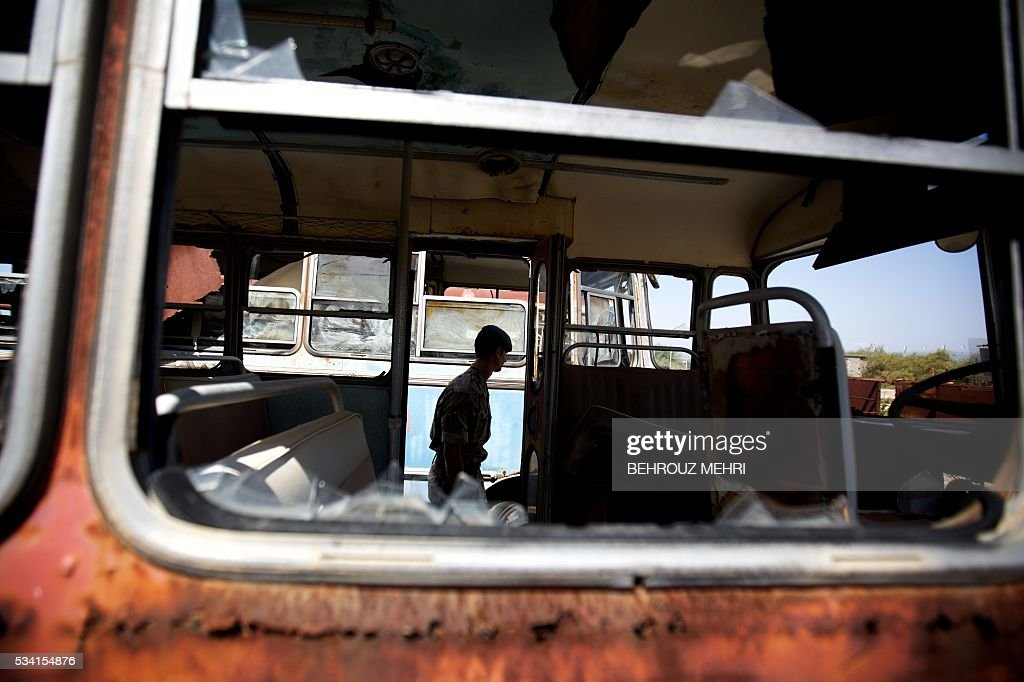 A picture taken through the window of a Bedford bus shows a British soldier walk among abandoned vehicles at the Sovereign Base Area of Akrotiri, a British overseas territory located ten kilometres west of the Cypriot port city of Limassol, on May 25, 2016. Abandoned in the streets of the base after the war, hundreds of vehicles that belonged to Turkish Cypriots, mostly dating from the 1960s, had been gathered in a vast wasteland in 1975 await their owners on the British base of Akrotiri, 42 years after being left behind in the divided island. The British authorities have recently undertaken an inventory of 400 vehicles in the hope of regaining their former owners, listing images and details of them on an internet site. / AFP / BEHROUZ