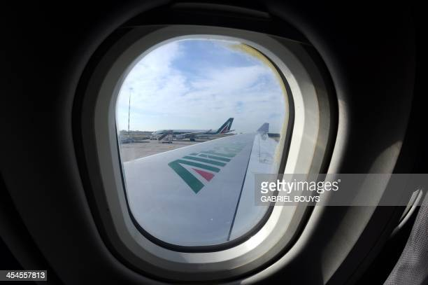 A picture taken through the window of an airbus A330200 shows the logo of the company Alitalia on the wing of the airplane on December 9 2013 at the...
