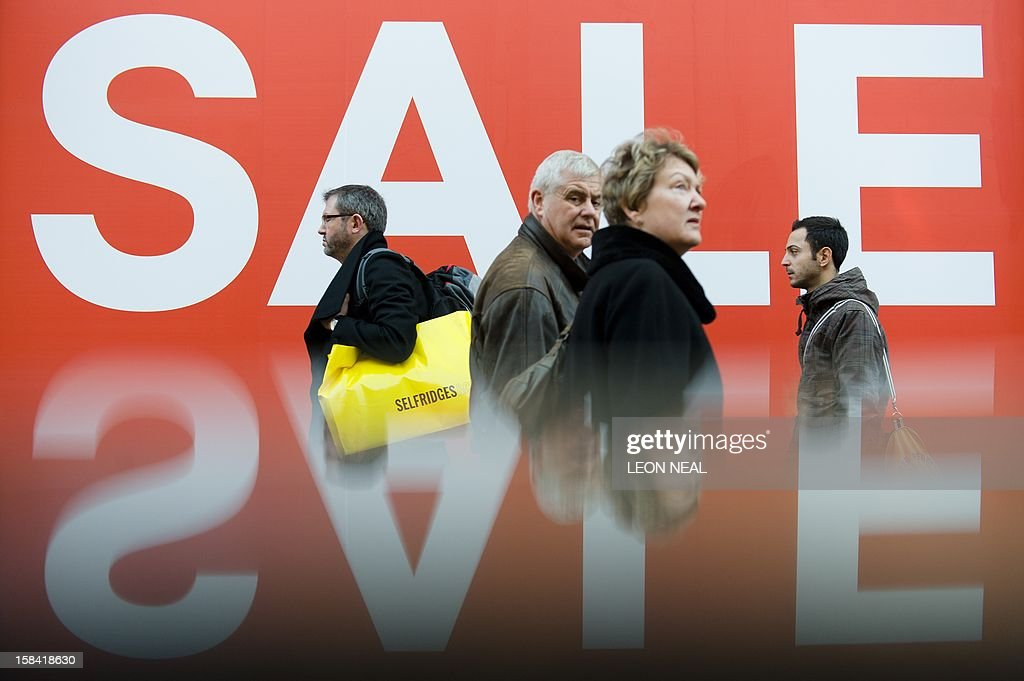 A picture taken using a pre-positioned reflective surface to produce the reflection shows shoppers passing a sign advertising an in-store sale in central London on December 16, 2012, less than two weeks before Christmas.