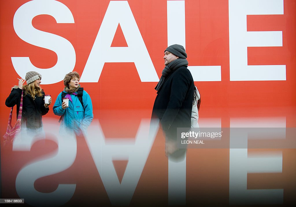 A picture taken using a pre-positioned reflective surface to produce the reflection shows pedestrians passing a sign advertising an in-store sale in central London on December 16, 2012, less than two weeks before Christmas.